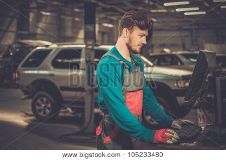 Specialist near car diagnostic pc in a workshop  poster