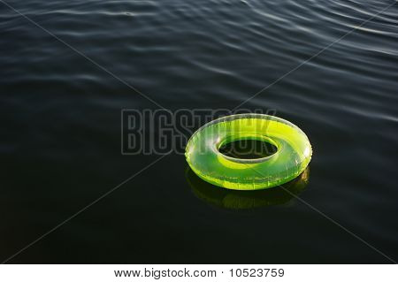 Lime Green Inflatable Ring Floating On Dark Water