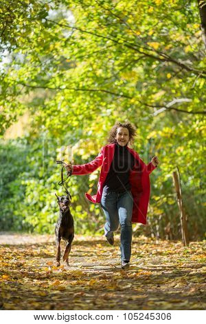 The woman in a red coat is running with a dobermann in wood.