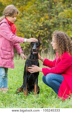 Little curly girl and her mother are walking the dobermann in park.