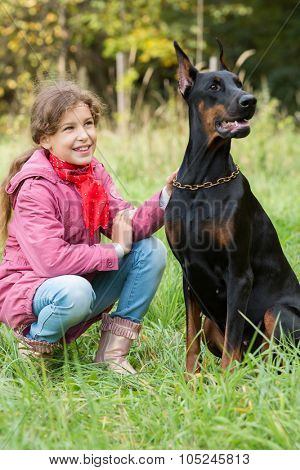 Little girl is smiling and sitting on the grass near a dobermann.