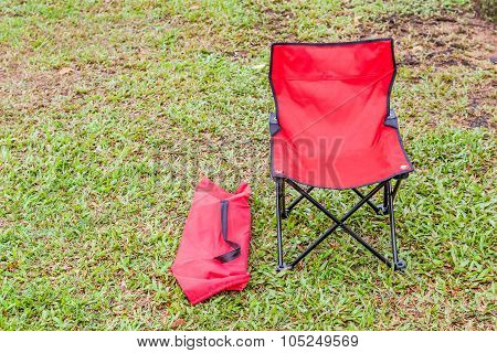Foldable Camping Chair With The Green Lawn Background.