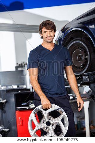 Portrait of confident technician holding metallic alloy at auto repair shop