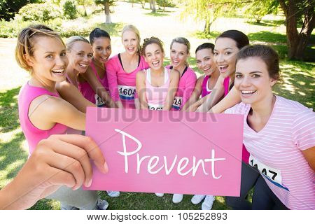 The word prevent and hand holding card against smiling women running for breast cancer awareness