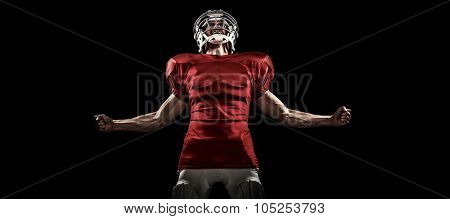 Aggressive American football player in red jersey screaming against black