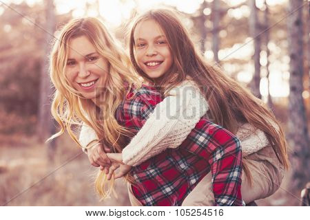 Mom and her 9 years old daughter spending weekend in the autumn forest together. Mother and child relations. poster