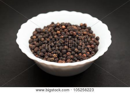 Organic Black pepper in white bowl.