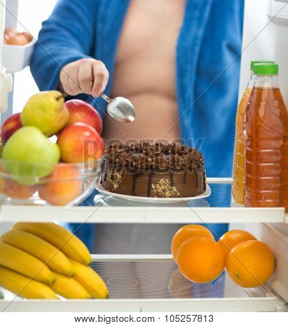 Obese guy prefer to eat big chocolate cake than fresh fruit in fridge