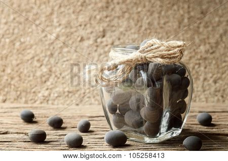 dialium cochinchinensis or velvet tamarind fruit in bottle glass on wood table poster
