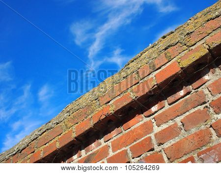 Bottom View On Top Of The Stone Wall Of Bricks Against A Blue Sky