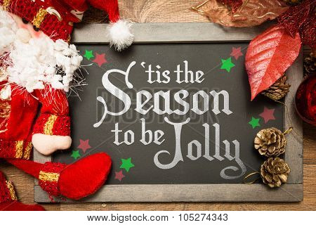 Blackboard with the text: Tis The Season to be Jolly in a christmas conceptual image