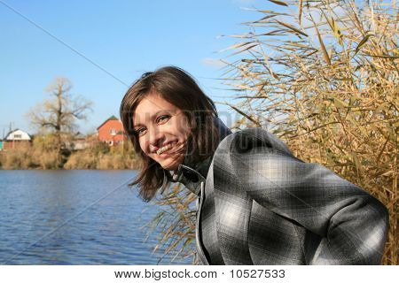 Молодая девушка улыбается против голубое озеро