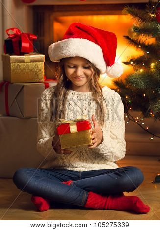 Smiling Girl Sitting On Floor And Looking At Christmas Presents