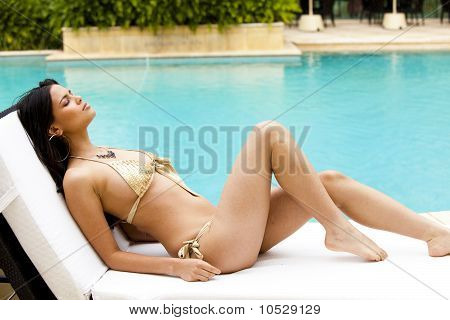 Young Woman Sunbathing Poolside In A Bikini