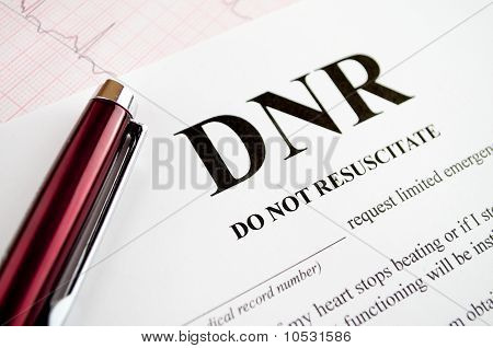 Do Not Resuscitate (DNR) form with pen and EKG tracing poster