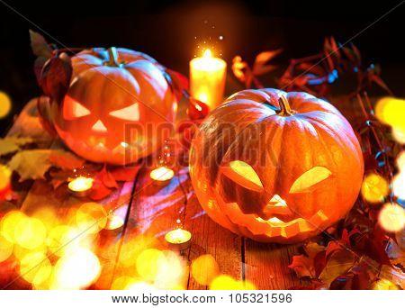 Halloween pumpkin head jack lantern with burning candles over black background. Halloween holidays art design, celebration. Carved Halloween Pumpkins with burning candles
