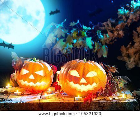 Halloween pumpkin head jack lantern with burning candles. Halloween holidays art design, celebration. Carved Halloween Pumpkins with burning candles in scary deep night forest