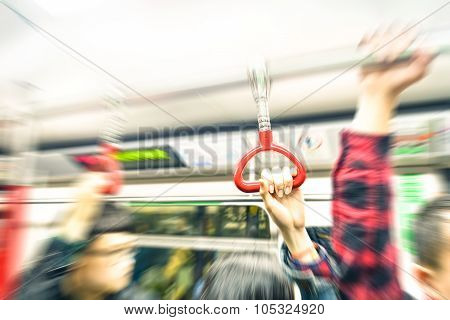 Concept of metropolitan transportation during rush hour - Hong Kong underground with radial zoom defocusing and vintage filtered look - Focus on the hand holding train handle during subway trip poster