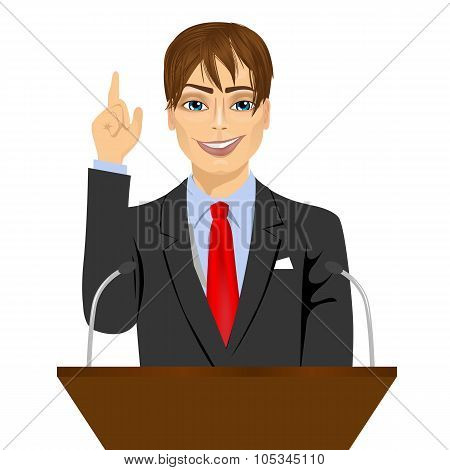 orator standing behind a podium with microphones
