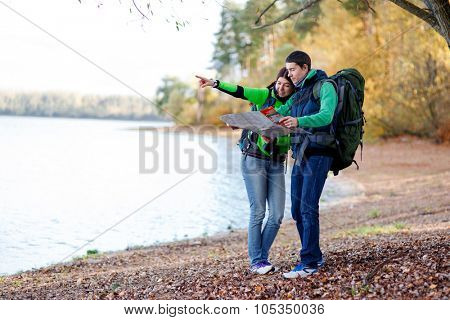 Happy couple on vacation navigating with map in forest