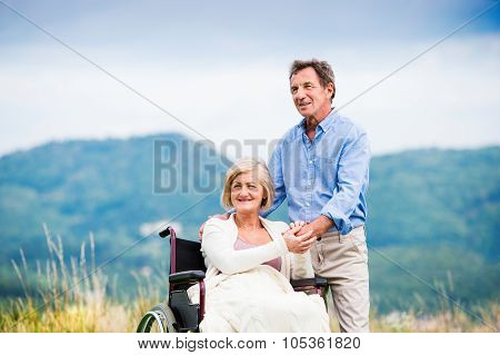Senior man with woman in wheelchair outside in nature poster