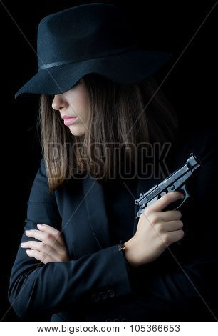 Beautiful Elegant Woman In Black Suit And Black Hat Holding Gun Isolated On Black Background