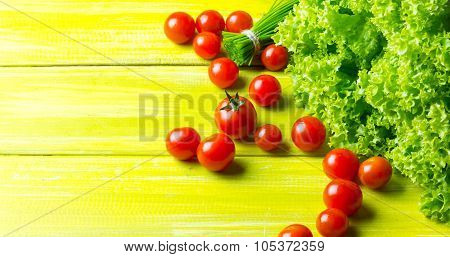 lettuce salad, tomatoes and chives on wooden green background.