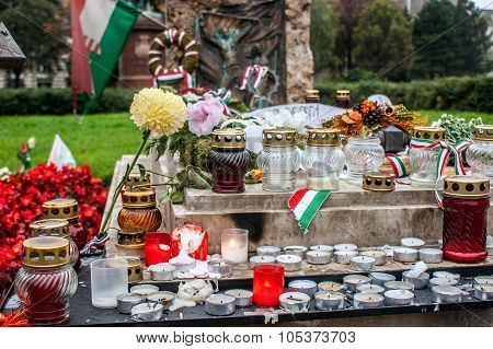 White candles, flowers of various colors and bows with the flag of Hungary in the grave of one of the victims of the Hungarian revolution of October 1956, in Budapest poster