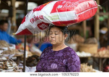 MANDALAY,MYANMAR,JANUARY 17, 2015 : A woman is carrying a large monosodium glutamate bag on her head in the street of Mandalay, Myanmar (Burma).