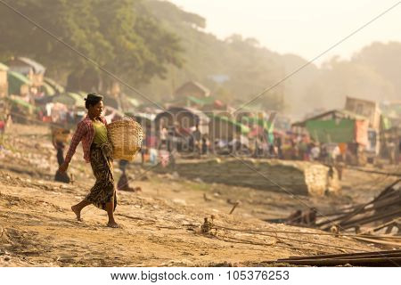 MANDALAY,MYANMAR,JANUARY 17, 2015 : A woman is carrying a basket , waling on a sloping ground and going to unload a boat of wooden planks in a slum area near the river in Mandalay, Myanmar (Burma).