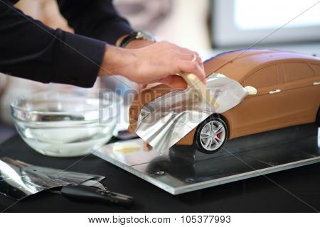 RUSSIA, MOSCOW -?? 4 DEC, 2014: A man sticks silver paper to the hood of model car at the press event for Ford in SREDA loft.