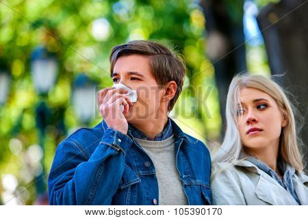 Man with cold rhinitis on autumn outdoor. Fall flu season. Girl looks with compassion on suffering of loved one.