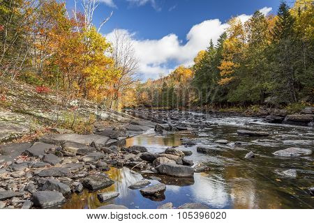 Autumn Colors Lining A Rock-strewn River