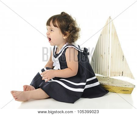 Profile of an adorable little girl angrily growing while sitting barefoot in her sailor dress.  A toy sailboat is behind her.  On a white background.