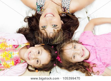 Young adorable hispanic sisters with mother lying down, heads touching and bodies spread out differe