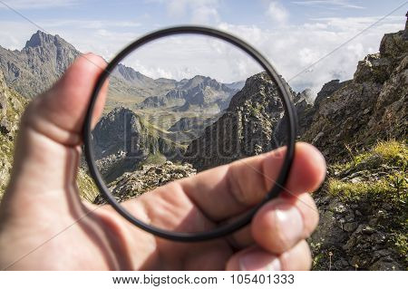 Hand puts a transparent clean protective UV filter to the camera
