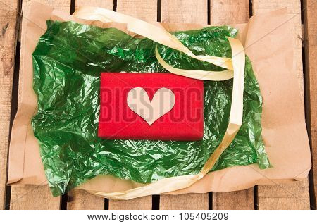 Nicely wrapped presents in red wrapping with golden heart lying on green plastic and brown paper, wo