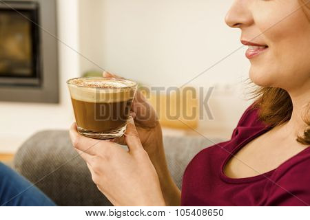 Beautiful woman at home drinking a capuchino