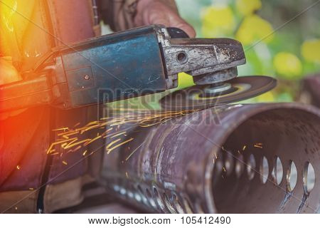 Worker Grinding Steel Pipe With Grinder