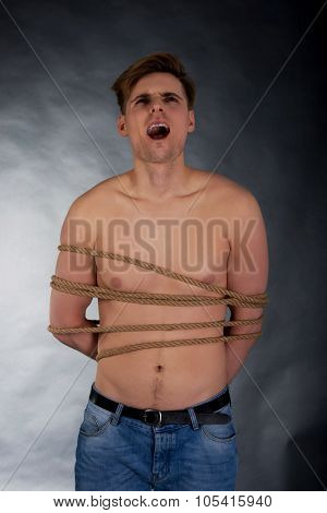 Tortured shirtless man tied with a rope. poster