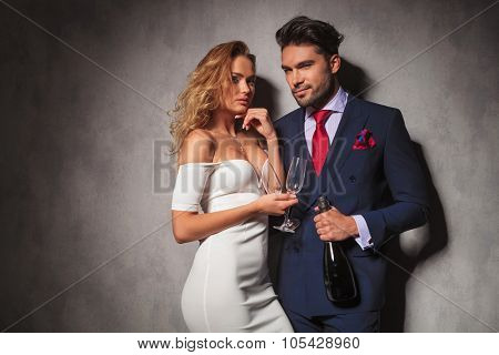 elegant couple ready to party with a bottle of champagne in studio