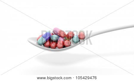 Colorful caplets inside a spoon, isolated on white background.