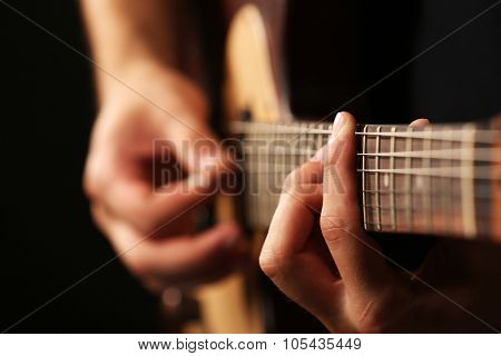 Young musician playing acoustic guitar close up poster