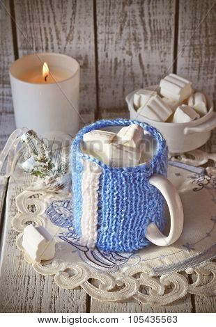 Mug with milk and marsmallow on the white table