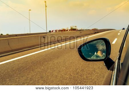 a young man, reflected in the wing mirror, driving a car in a road with several lanes