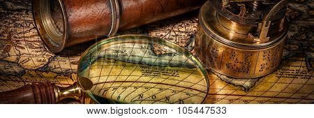 Travel geography navigation concept background - letterbox panorama of old vintage retro compass with sundial, spyglass and magnifying glass on ancient world map