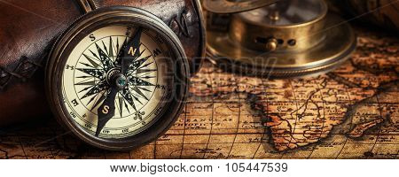Travel geography navigation concept background - letterbox panorama of old vintage retro compass with sundial, spyglass and rope on ancient world map
