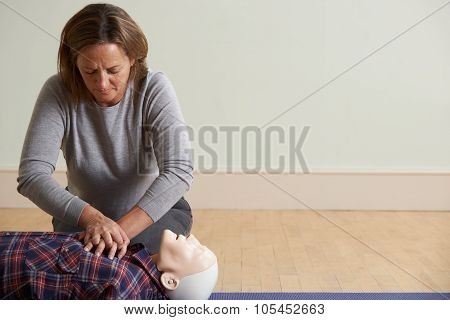 Woman Using Cpr Technique On Dummy In First Aid Class