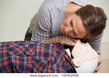 Woman In First Aid Class Checking Airway On CPR Dummy poster