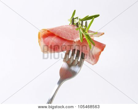 slice of smoked pork neck with rosemary impaled on fork